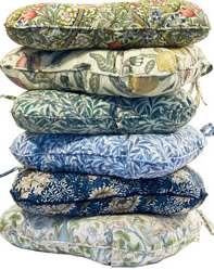 A stack of cushions covered in foliate and floral William Morris textiles
