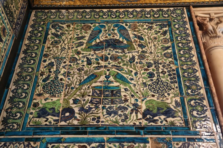 Blue white and green Damascus wall tiles, with parrots drinking from a fountain, and vases of stylised tulips, with a busy foliate background
