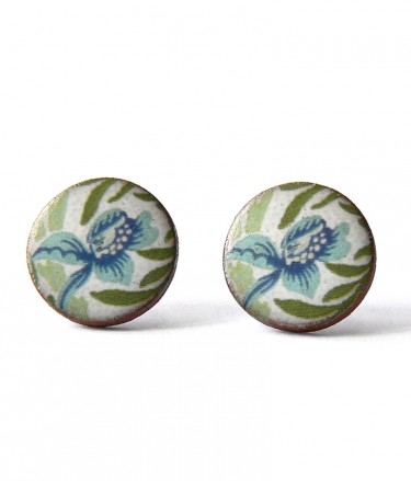 A pair of round stud earrings with blue flowers and green leaves