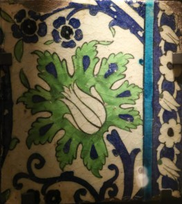 A glazed ceramic tile with a stylised tulip motif with a green foliate background and blue decoration