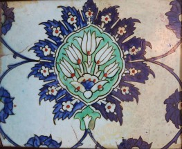 A ceramic tile with a central floral motif of five stylised tulips on a green background
