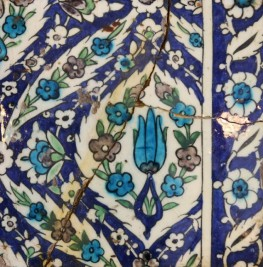 A blue, white and green glazed tile with a stylised tulip and abundant floral decoration