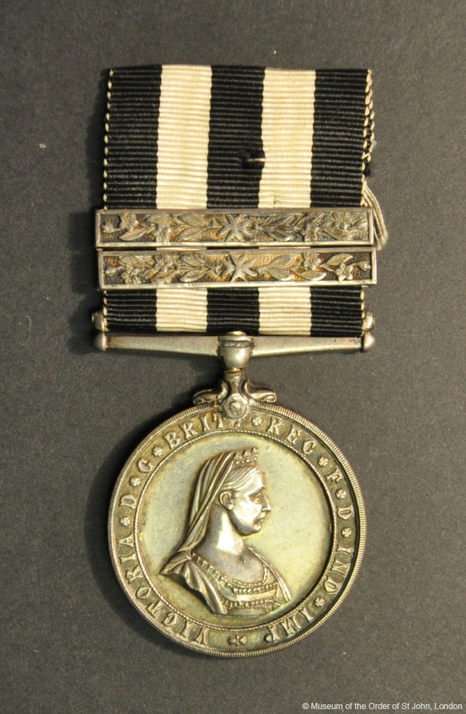 A round silver medal with a profile portrait of Queen Victoria, suspended from a black and white striped ribbon and two silver bars decorated with a central eight-pointed cross and St John's Wort.