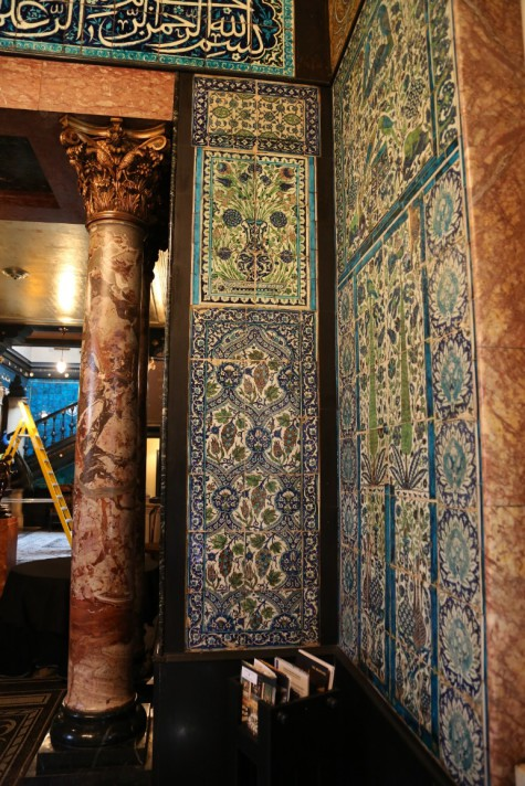 A view of blue, white and green Damascus wall tiles, and a marble pillar