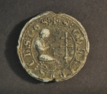 a round seal showing a human figure kneeling before a cross with a legend around the border