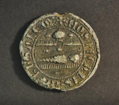 a round seal with a horizontal human figure lying beneath a canopy of architectural detail with legend around the border