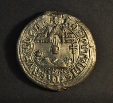 a round seal showing a horizontal human figure lying below an architectural canopy with a legend in a border around the edge