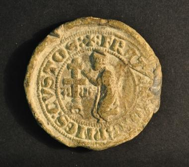 a round seal showing a human figure kneeling before a cross with a legend in a border around the edge
