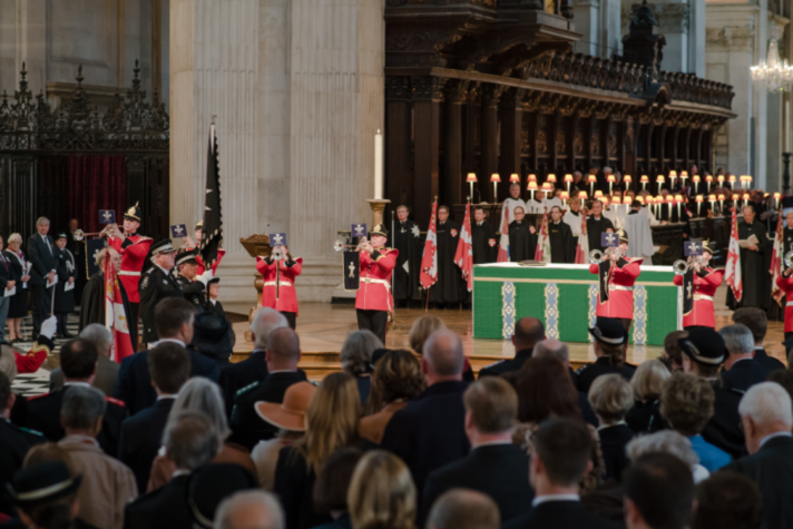 """ALT=""""Members of a brass band in red play during the St John's Day service at St Paul's Cathedral"""""""