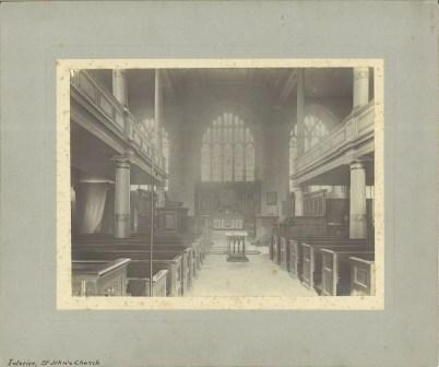 A black and white photograph of a church interior, looking towards the altar at the east end, with large windows, pews and mezzanine levels