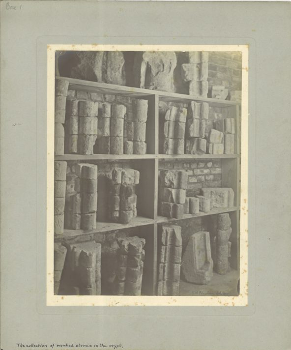 a black and white photograph of fragments on stone displayed on shelves