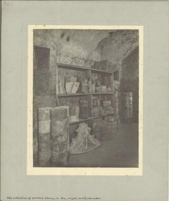 A black and white photograph of fragments of stone display on shelves and arranged on the floor