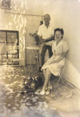 """ALT=""""Sepia photograph of man standing beside seated woman on patio, dog lying at woman's feet"""""""