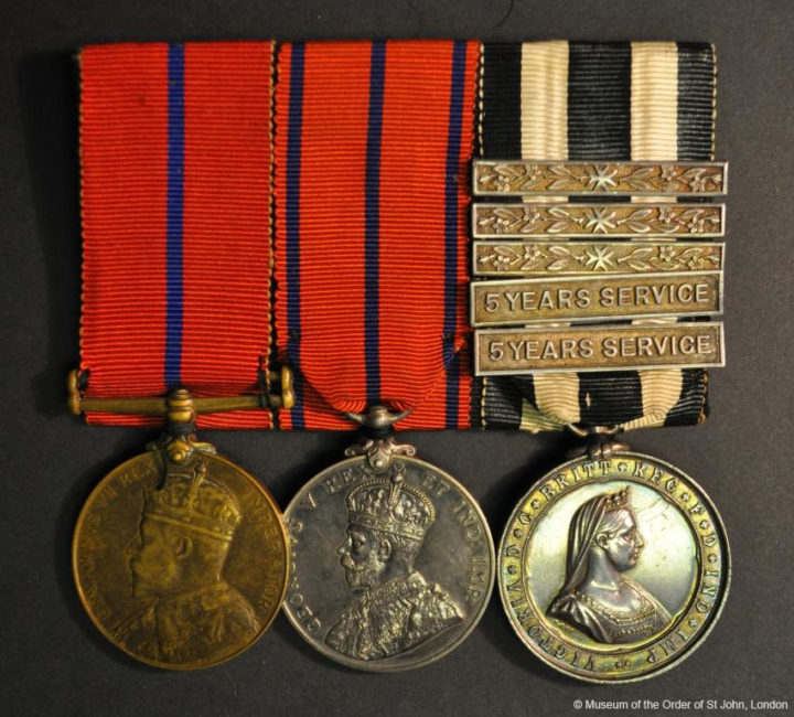 Three court-mounted medals. The first is a round bronze medal with a profile portrait of Edward VII suspended from a red and blue ribbon. The second is a silver round medal with a profile portrait of George V suspended from a red and black ribbon. The third is a round silver medal with a profile portrait of Queen Victoria suspended from a black and white striped ribbon with five clasps.