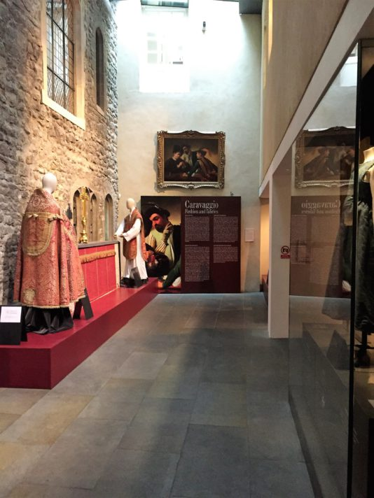 "ALT=""view of Caravaggio Fashion and Fabrics exhibition with painting in centre, text panel below and altar and mannequins showing historic fabrics on left"""