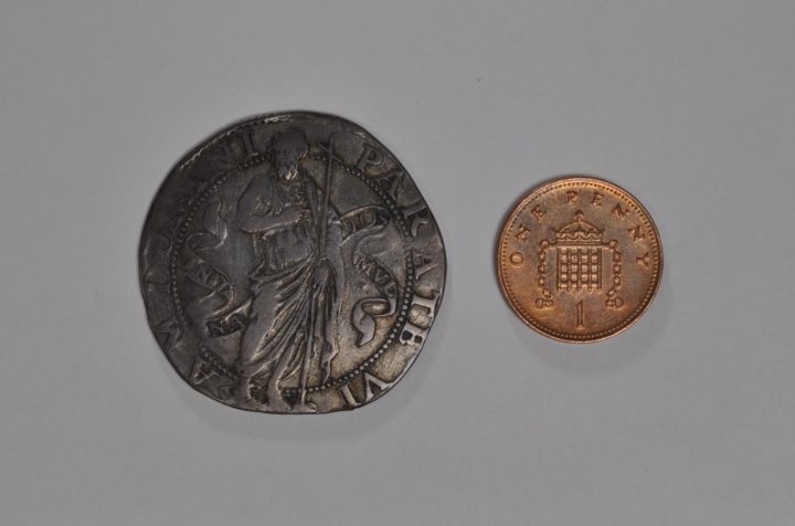 A coin minted under Jean de Vallette next to a modern one pence piece, to demonstrate the size of the old coin