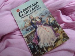 "ALT=""Cover of Barbara Cartland's novel 'The Dream and the Glory' showing sailor holding a lady in a pink dress on the deck of a ship during a battle"""