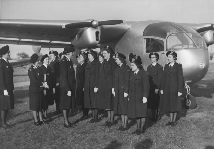 Black and white photograph of the inspection of the Berkshire Air Unit, approximately 14 female volunteers stand in two lines in front of an aeroplane whilst four higher ranking female officers, including Susie George, inspect them.