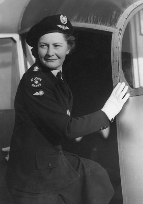 Black and white photograph of Susie George in uniform looking back whilst stepping into an aeroplane