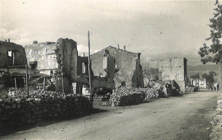 Black and white photograph of half destroyed buildings, many missing walls and roofs, next to a small dirt track road.