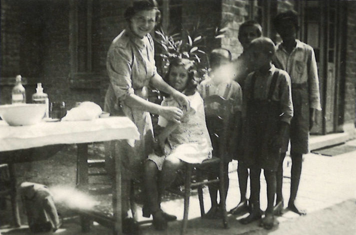 Black and white photograph of Susie George standing next to a medical table, facing the camera and smiling whilst giving a child inoculations.