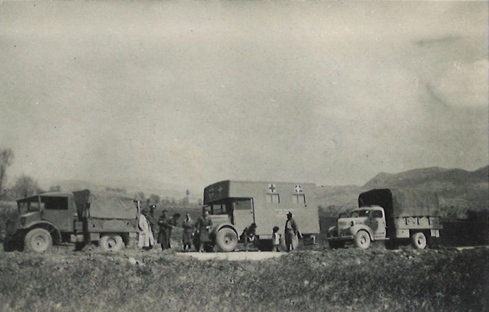Black and white photograph of three military trucks in a line, the middle vehicle is the mobile clinic with the symbol of the red cross on the front and side.