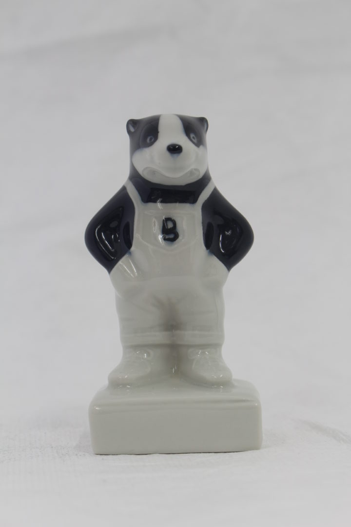 """Small Model Badger wearing dungarees with a """"B"""" on his chest."""