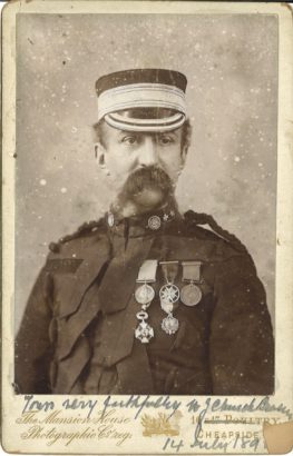 A black and white portrait photograph, half length, of a man with mostache in a uniform with hat and medals