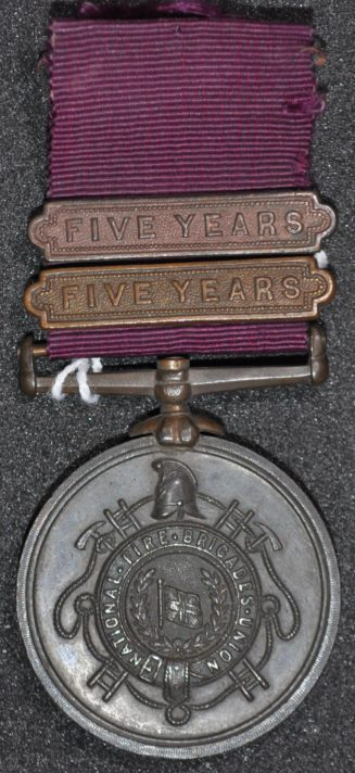 Round silver coloured metal on a maroon ribbon. Two five year bars attached to the Ribbon. Medal depicts garter bearing teh words 'National Fire Brigades Union'. In the center of the garter is a flag underlined by a wreath. Surrounding the garter is a helmet, two ladders, rope and two pick axes.