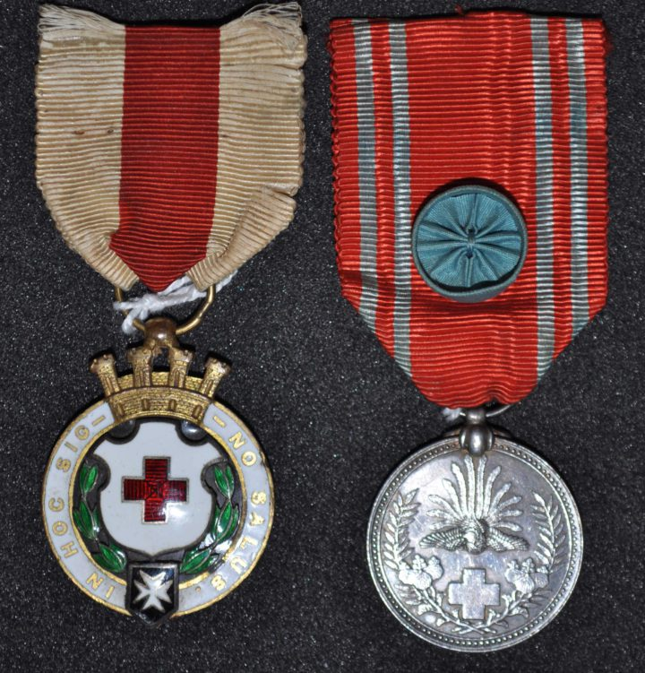 Left hand medal round with white rim bearing an inscription. Crown on top and shield in middle. On a white and red ribbon. Right hand medal a round silve coloured medal with a cross and flora on it. Red and white ribbon with blue button in middle.