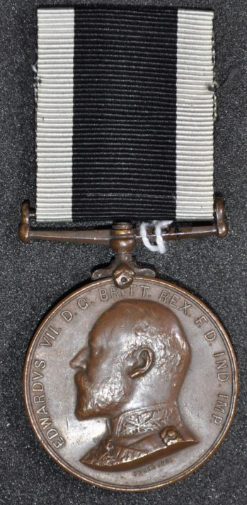 Round bronze coloured medal with a portrait bust. Ribbon has a large black stripe with two thinner white stripes either side.
