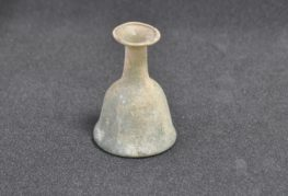 A Roman vessel with a slightly asymmetrical bell-shaped base and an everted lip. Blue-green in colour.