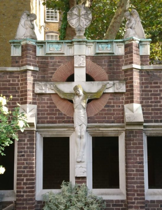 Christ on a large cross. Two angels look down on him in prayer and symbol of the Order above him.