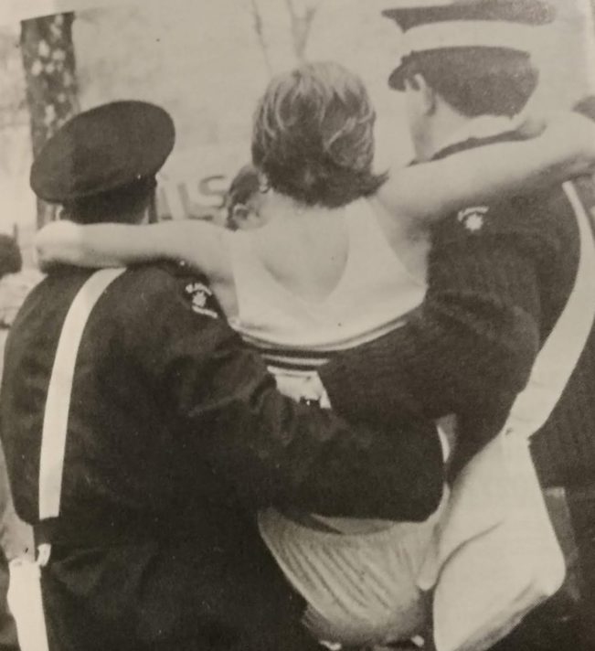photograph of a runner being carried by two St John men