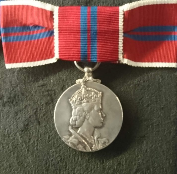 Medal with the queens face on it attatched to a ribon that is red with two small blue stripes. It is tied in a bow shape and has a white trim.
