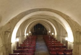 Image of the crypt looking down the nave. Low arches can be seen leading towards an alter and a large window.