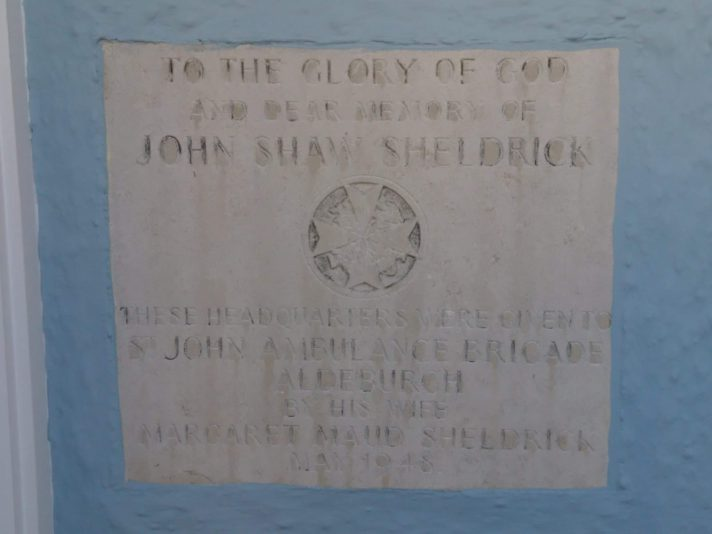"Plaque on Aldeburgh High Street that reads ""To the Glory of God and dear memory of John Shaw Sheldrick. These Headquarters were given to St John Ambulance Aldeburgh by his wife Margaret Maud Sheldrick, Jan 1948"