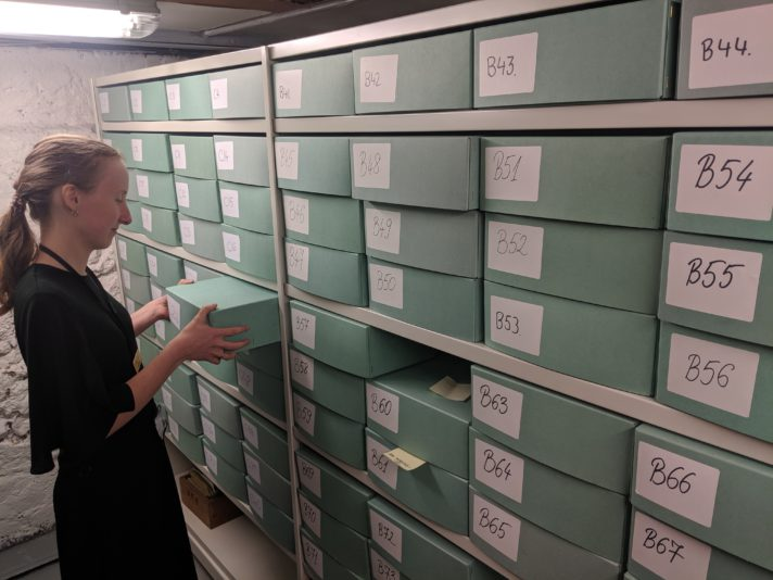 Girl taking a box off a shelf of archival boxes