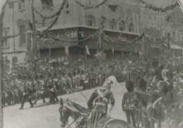 Black and white photograph of a procession. Some stretcher bearers are carrying a casualty in the street.