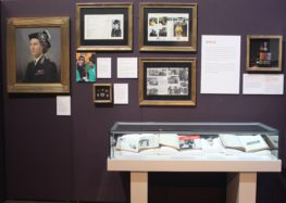 Photograph of an exhibition with several framed items on the wall