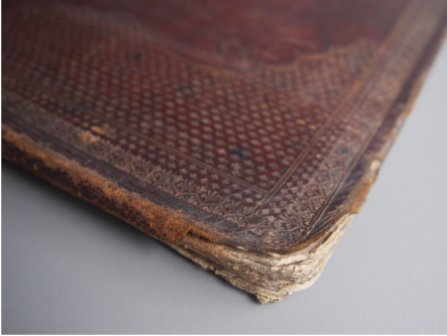Before treatment - the damage to the edges of the leather bound board shows the layers coming apart beneath.