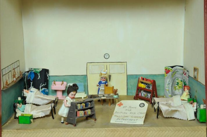 A diorama with toy people, two volunteers giving out books to patients in bed.