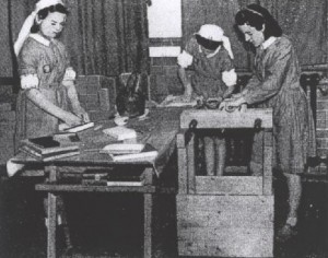 Back and white photograph of three young women in uniform tending to books