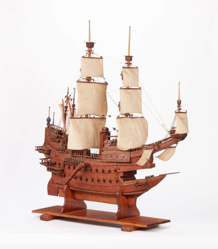 Photograph of a wooden model ship with cotton sails.
