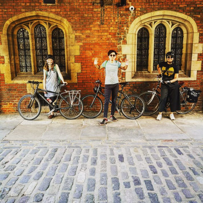 Photograph showing three people standing with bikes under St John's Gate
