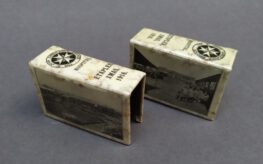 Two matchboxes branded with the St John Ambulance logo and with photographs of a wartime hospital.