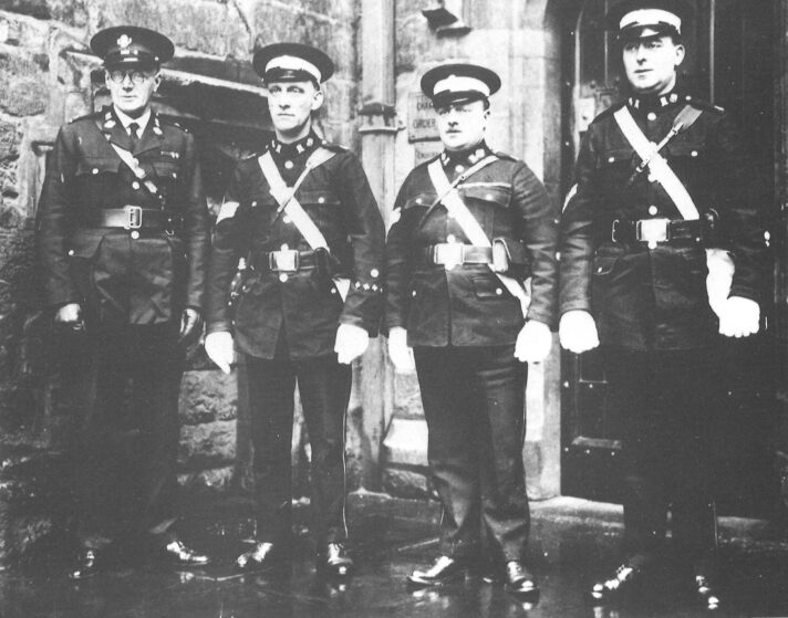 Black and white photograph of four men in St John uniform standing in a row.