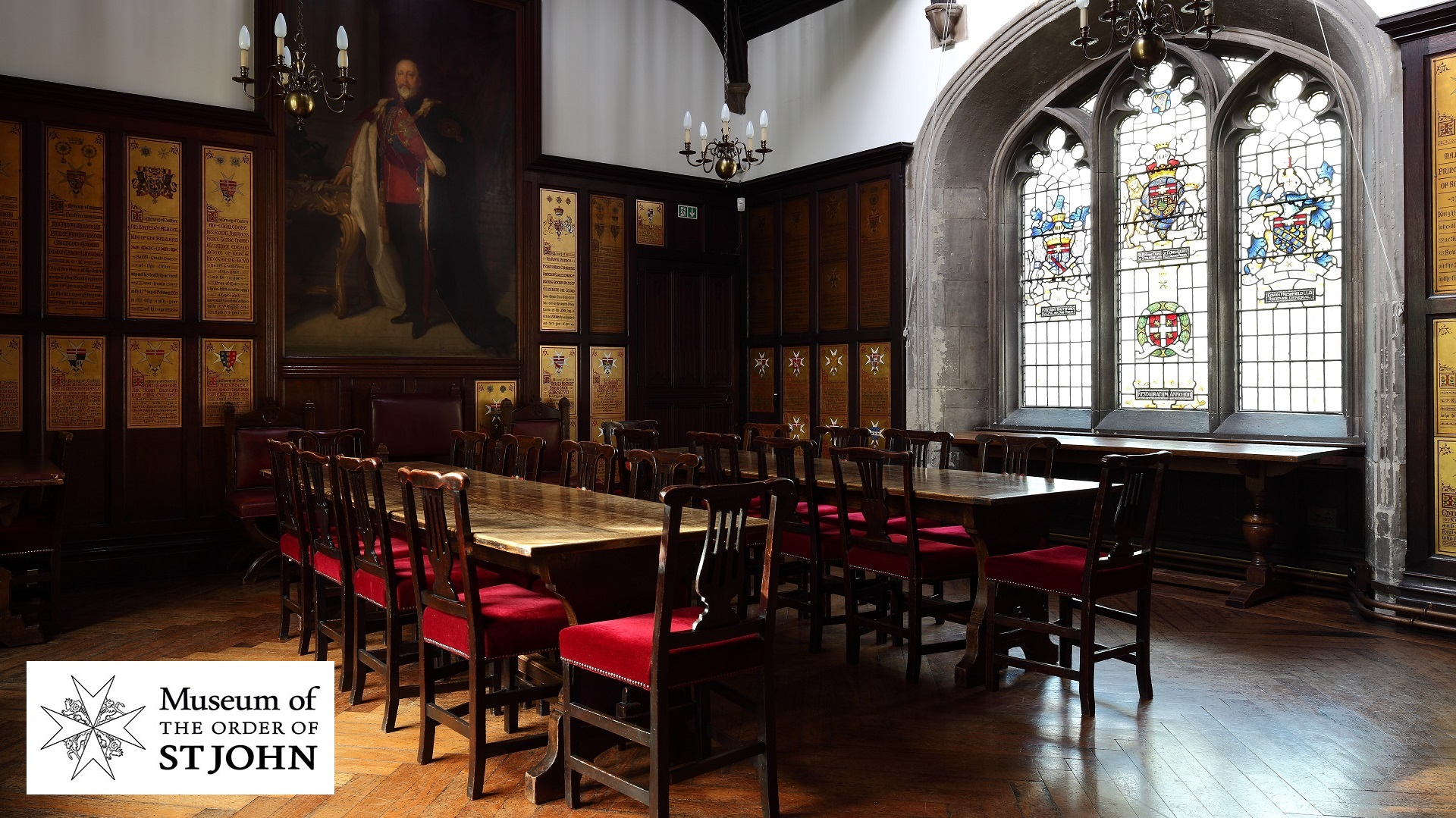 Photograph of a panelled room with a portrait oil painting on one wall and stained glass windows in another.