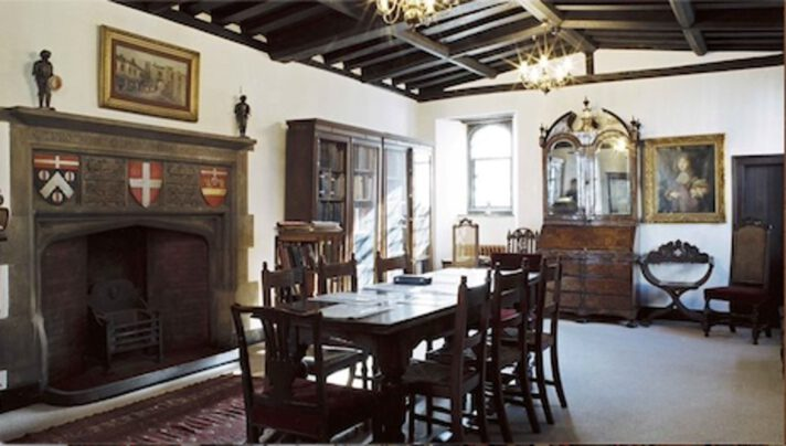 Photograph of a room with a a grand fire place, a table and chairs in dark wood in the middle and some cabinets full of books.